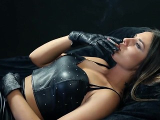 A hot brunette girl in leather smokes a cigarette. - Hot body and hot tits!