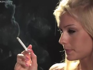 A blonde girl smokes a cigarette. She knows she has a hot body and is sexy.