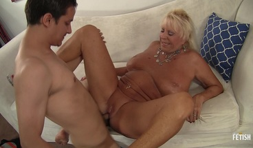 Granny with huge boobs rides a big white dick on the couch